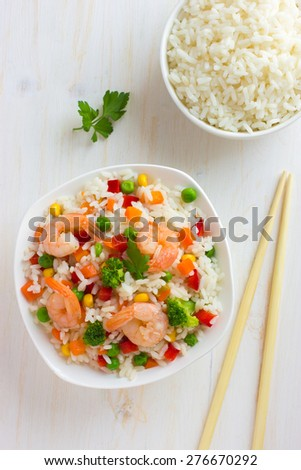 Rice with vegetables and shrimps on white background, top view