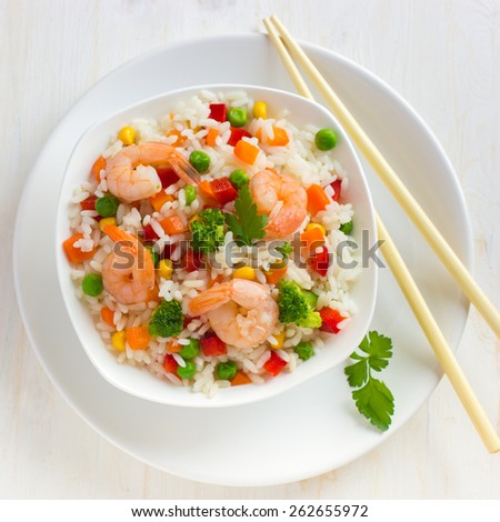 Rice with vegetables and shrimps on white background, top view, square image - stock photo