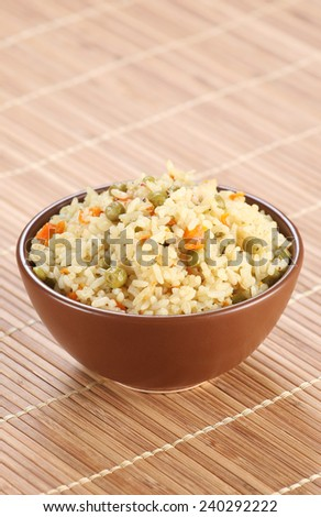 rice with vegetables in a ceramic bowl on a mat bamboo background - stock photo