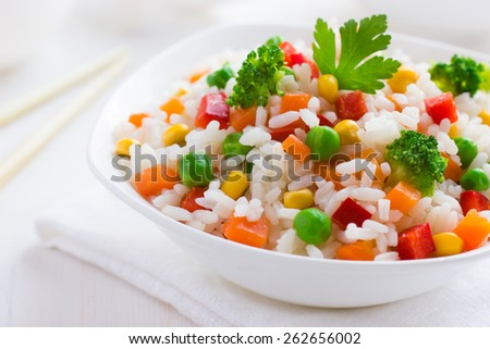 Rice with vegetables on white background - stock photo