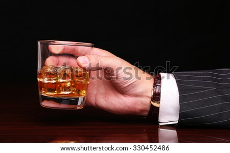 rich and success business man holding in hand glass of alcohol scotch whiskey with ice cube on wooden table and black background - stock photo