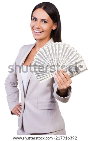 Rich and successful. Happy young businesswoman in suit showing money and smiling while standing against white background