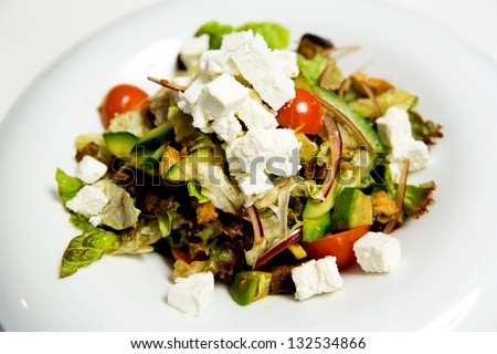Rich breakfast decorated with salad inclusive of tomatoes, avocado and feta cheese. - stock photo