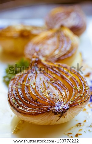 Rich brown roasted caramelized balsamic onions on a plate. - stock photo