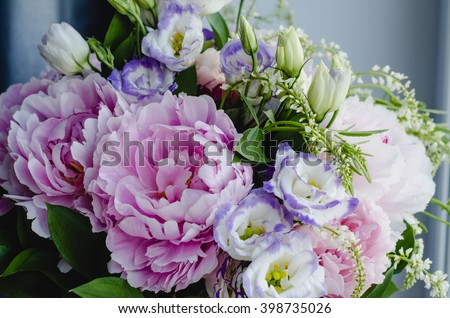 Rich bunch of pink peonies and lilac eustoma roses flowers, green leaf in glass vase. Fresh spring bouquet. Summer Background - stock photo