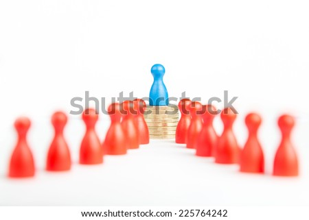 Rich business leader concept with blue figure on top of coin stack as a symbol of wealth on white - stock photo