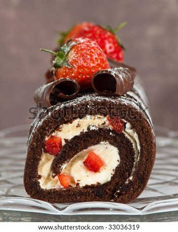Rich chocolate swiss roll decorated with strawberries on glass comport - stock photo