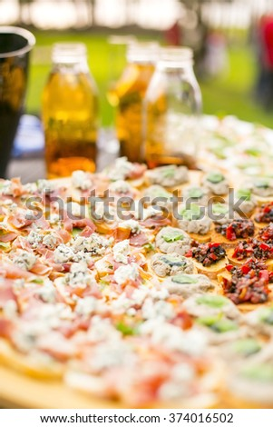 Rich choice of finger food bruchettas and apple juice on a picnic table - stock photo