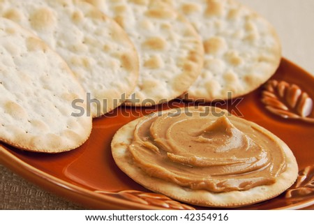 Rich creamy and delicious swirl of peanut butter on a cracker - stock photo