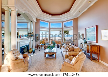 RIch furnished living room with coffered ceiling and colomns. Floor-to-ceiling angled window open a charming view on mountains