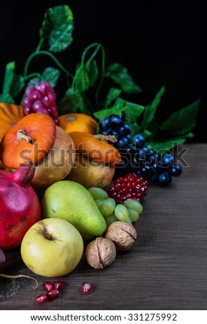 Rich harvest of various fruits and vegetables: decorative pumpkins, squash, apples, pears, pomegranates and grapes on the dark wooden background - stock photo