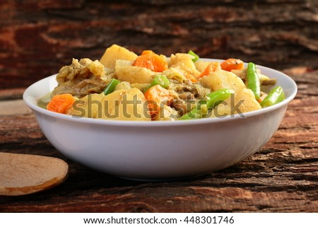 Rich hearty beef stew ready to serve.on wooden background.