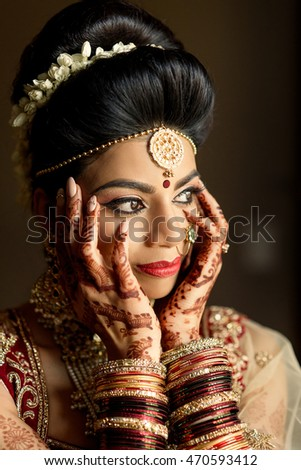 Rich Indian bride holds her hands covered with mehndi over her cheeks