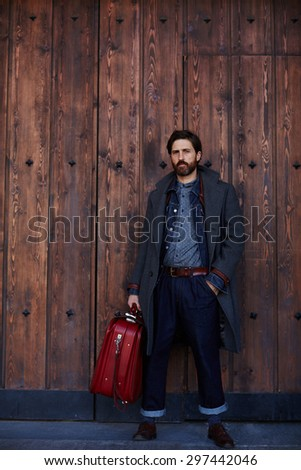 Rich successful man with beard hold vintage travel bag standing against wooden wall background with copy space for your text message, male traveler or tourist in a autumn clothes waiting for the train