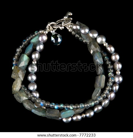 Richly colored and luminous, custom designed pearl and gem stone bracelet. Isolated on black background.