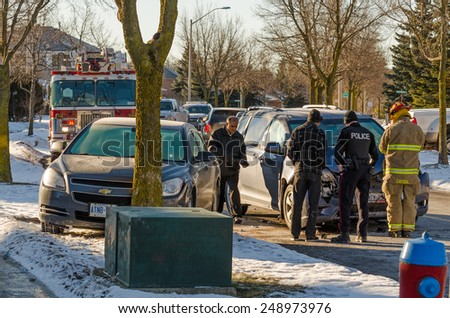 RICHMOND HILL, ONTARIO - JANUARY 28, 2015: Police and Firemen at the scene of an automobile accident on a residential street in Richmond Hill in Ontario.