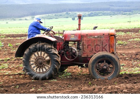 Richmond, KwaZulu Natal, South Africa - December 7, 2014: Unknown man demonstrating Vintage tractor at Natal Vintage Tractor and Machinery Club at Baynesfield Estate in Richmond, KwaZulu-Natal,