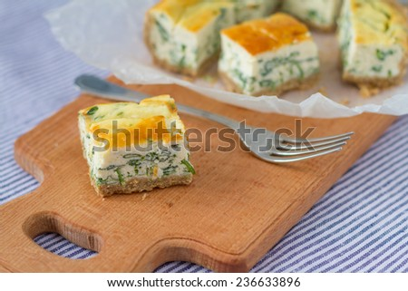 RIcotta, spinach quiche pie - one piece closeup on wood board - stock photo