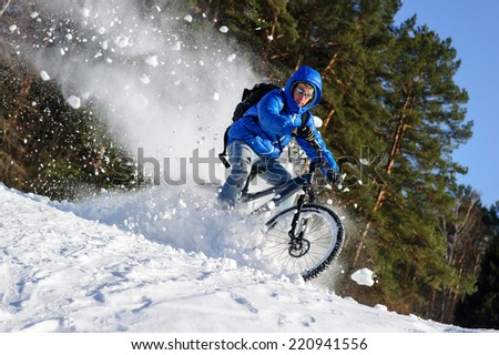 Rider cycling on a mountain bicycle in the snow in the winter forest - stock photo