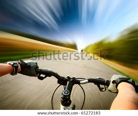 Rider driving bicycle on an asphalt road. Motion blurred background - stock photo