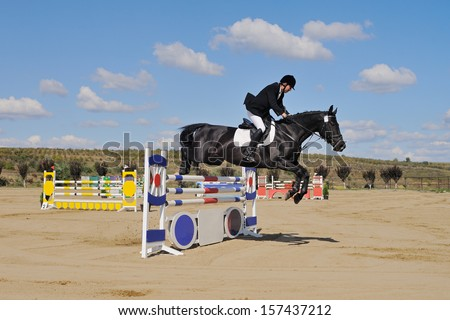 Rider on BLACK horse in jumping show - stock photo