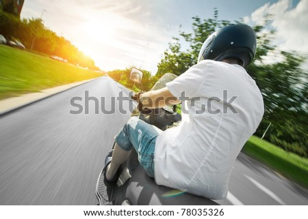 Rider on scooter riding in city - stock photo