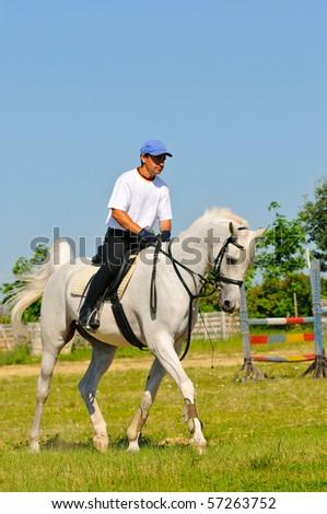 Rider on white sportive arabian horse - stock photo