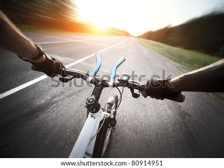 Rider's hands in gloves on a bicycle handlebar. Motion blurred - stock photo