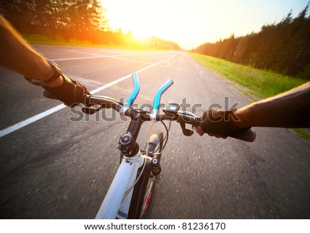 Rider's hands in gloves on a bicycle handlebar. Motion blurred asphalt road - stock photo