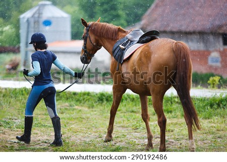 Rider with the horse in the rain at summer time - stock photo
