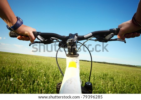 Riders hands holding handlebar on a green meadow - stock photo