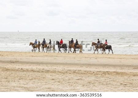 riders on horses on the beach close to North sea - stock photo