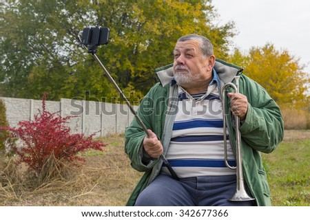 Ridiculous senior man making faces while doing selfie outdoor - stock photo