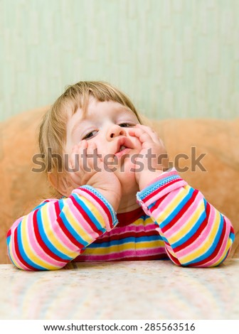 Ridiculous thinking little girl at home - stock photo