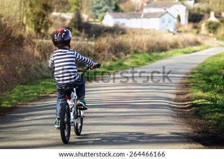 Riding a bicycle on a country road concept for healthy lifestyle, exercising and road safety - stock photo