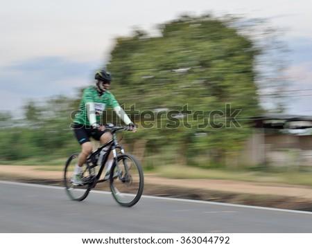 Riding a bike on a street  motion blur  - stock photo