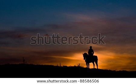 Riding a horse in sunset - stock photo