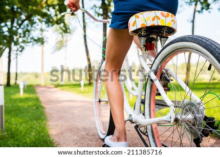 Riding bicycle in park. Close-up of young woman riding bicycle in park - stock photo