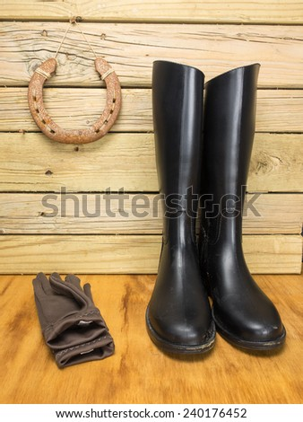 riding boots and gloves in against a stable wall with horseshoe