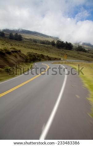 Riding down Haleakala highway in Haleakala National Park, Maui on a bike. Motion blur in foreground. - stock photo