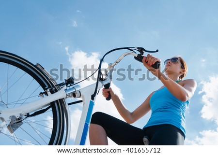 Riding electric bicycle or e-bike, shot against blue sky, convenient copy space - stock photo