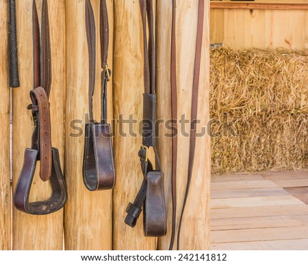 riding horse equipment hang on wooden fence - stock photo