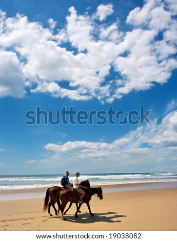 Riding Horses on the Beach - stock photo