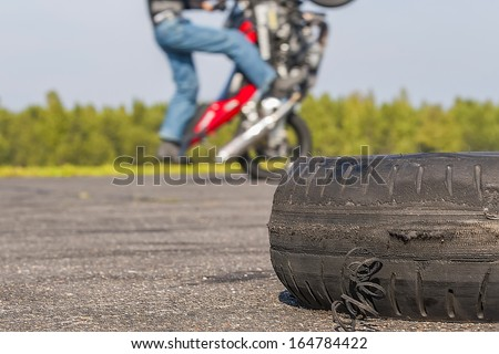 Riding on one wheel motorcycle and worn tire in the foreground. - stock photo