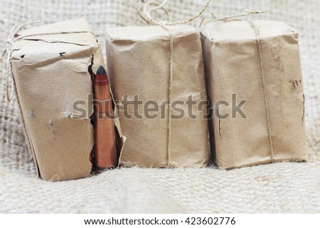 rifle bullet in old wrapping paper, a packaging factory ammunition. - stock photo