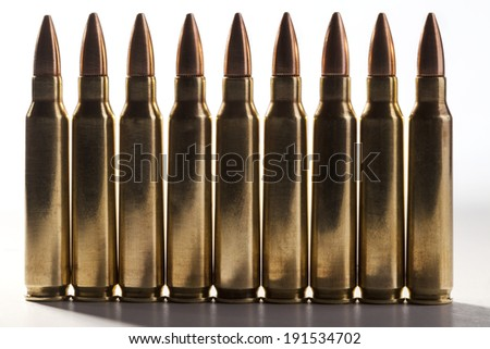 Rifle bullets in a row with shadow on white background