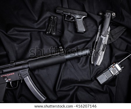 Rifle, gun, knife with sheath, compass and notebook with pen on on black cloth