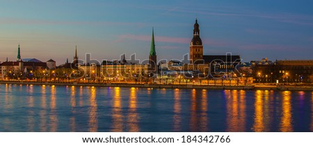 Riga (Latvia, Baltic States)  at night. Panoramic cityscape of the biggest city in Baltic States. The view to Old Town from Daugava river. Roofs of medieval churches and other historical  buildings. - stock photo