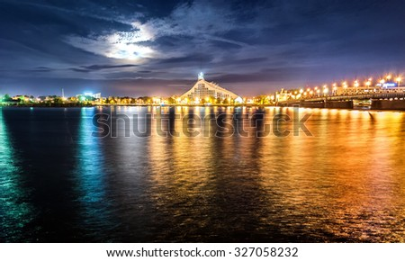 Riga, Latvia. Bridge with view of  The National Library of Latvia and Daugava river and bridge at night with moon, stars and night lights