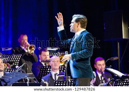 RIGA, LATVIA - December 9: American jazz vocalist, composer and lyricist Kurt Elling performing with Latvian Radio Big Band on stage at Riga's Congress Hall on December 9, 2012 in Riga, Latvia. - stock photo